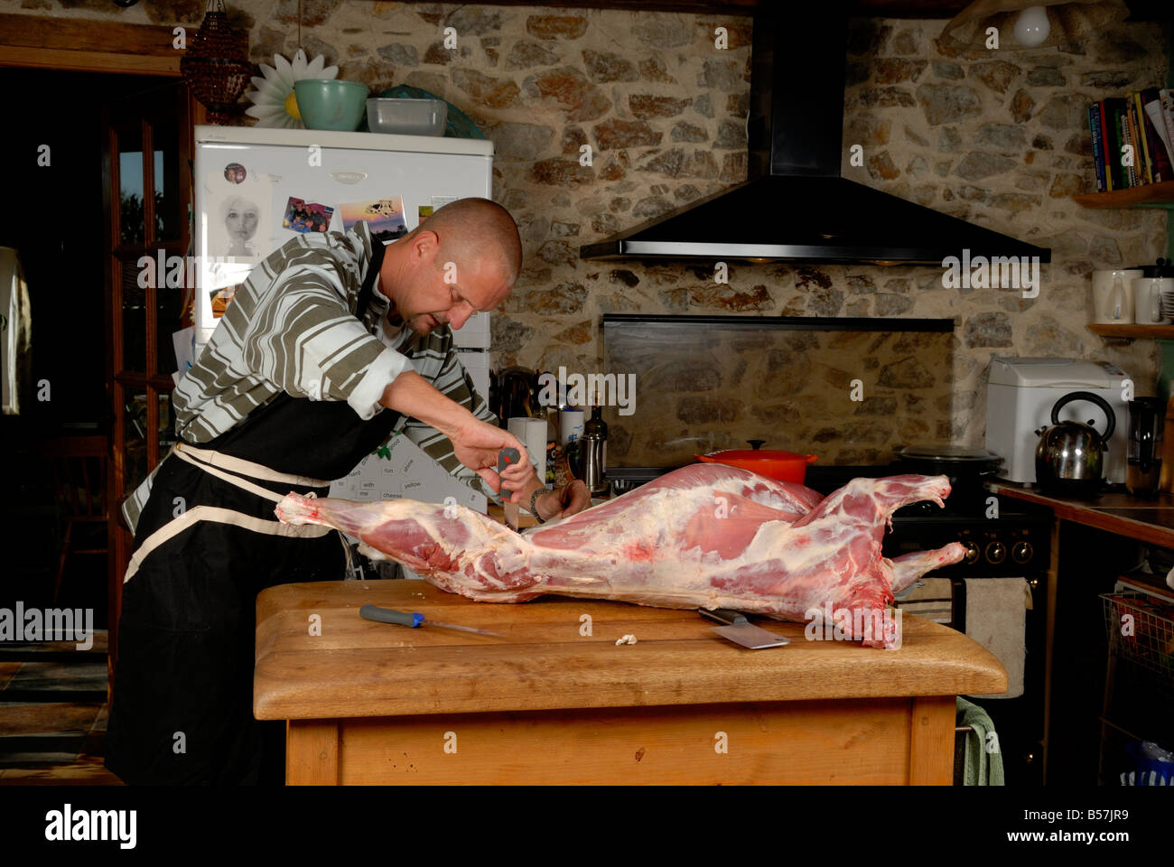 Stock photo of a man butchering a lamb in his Kitchen on a wooden table - Stock Image