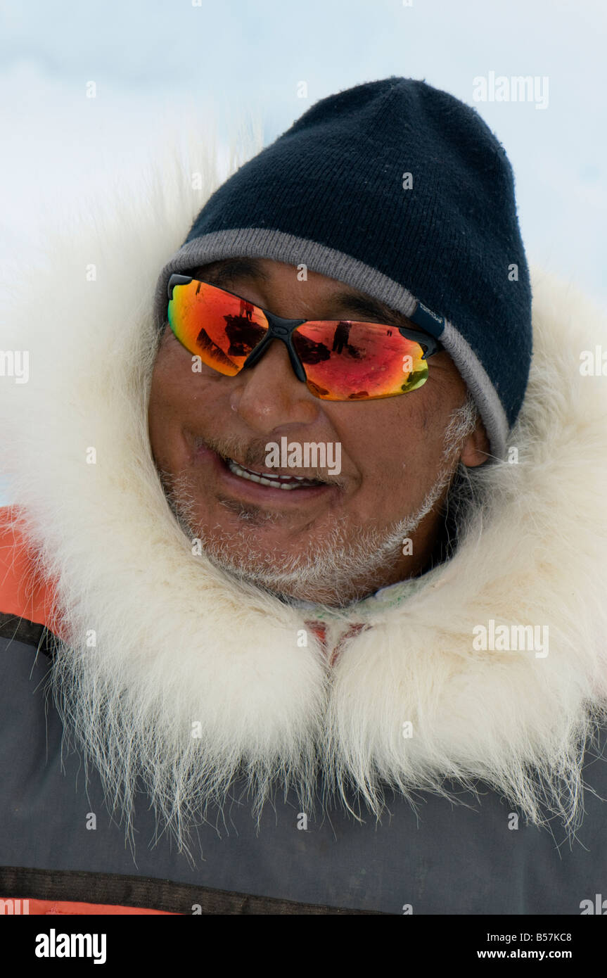 Inuit hunter Jake Awa of Pond Inlet wearing a traditional parka The hood is trimmed with polar bear fur - Stock Image