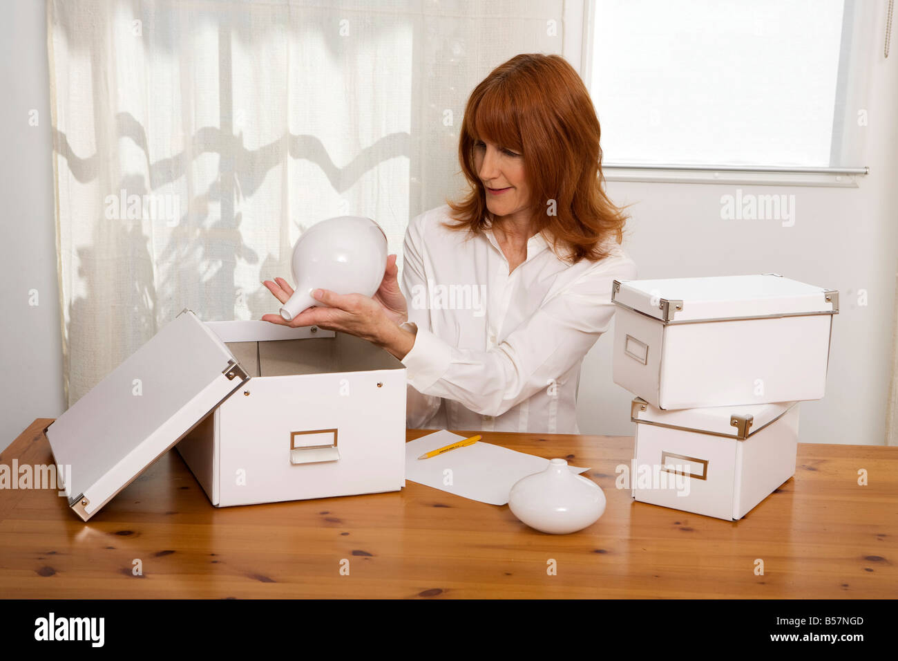 red haired woman 40 -50 years organizes objects in the house - Stock Image