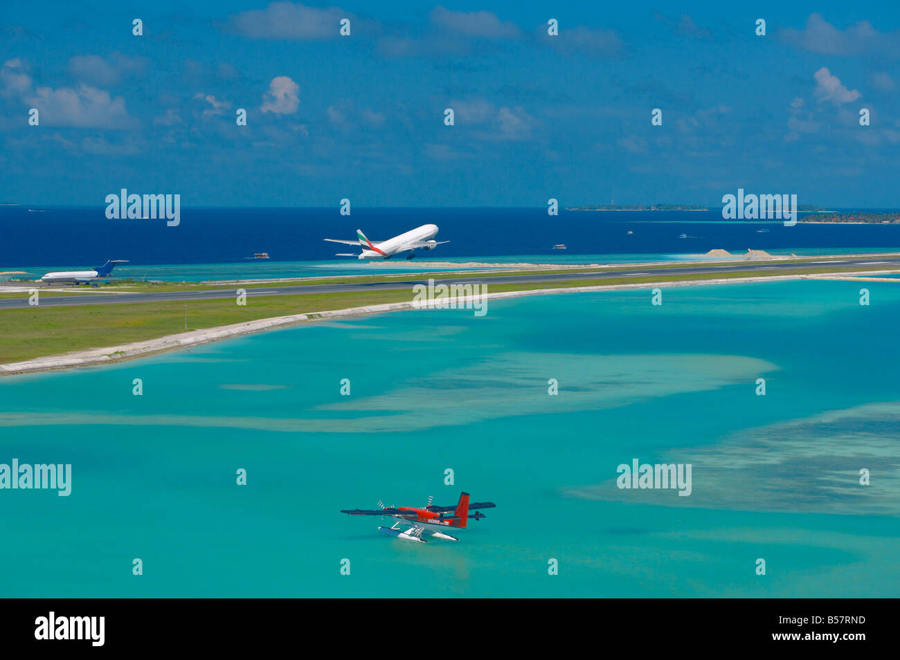 Passenger jet taking off from Male International Airport, and Maldivian air taxi ready to take off, Maldives, Indian Stock Photo