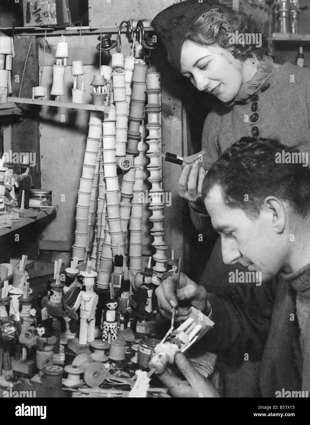 Man at work making cotton reel dolls watched by his wife. February 1938 