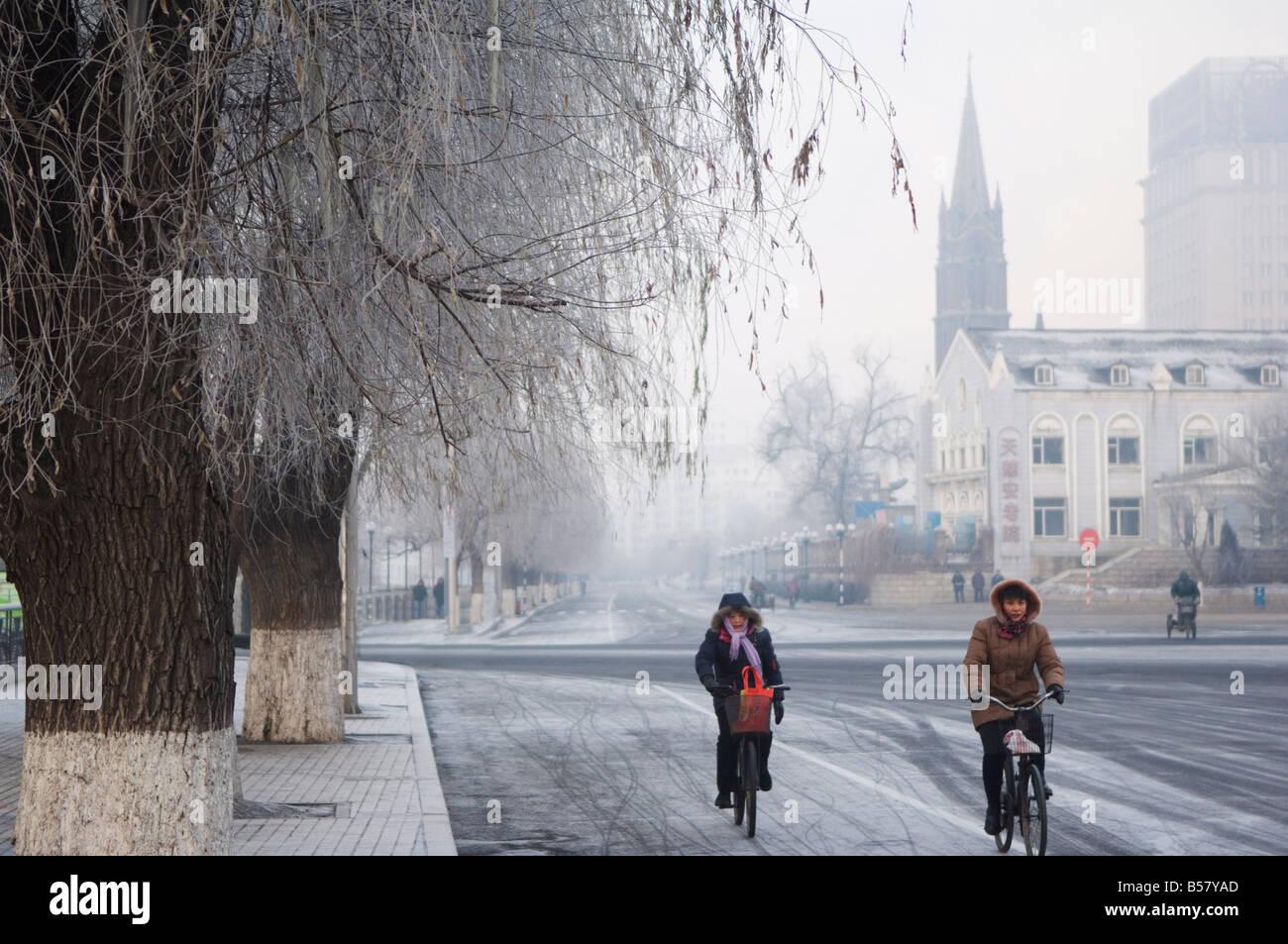 Cyclists in a winter wonderland and Catholic church in Jilin City, Jilin Province, Northeast China, China, Asia - Stock Image