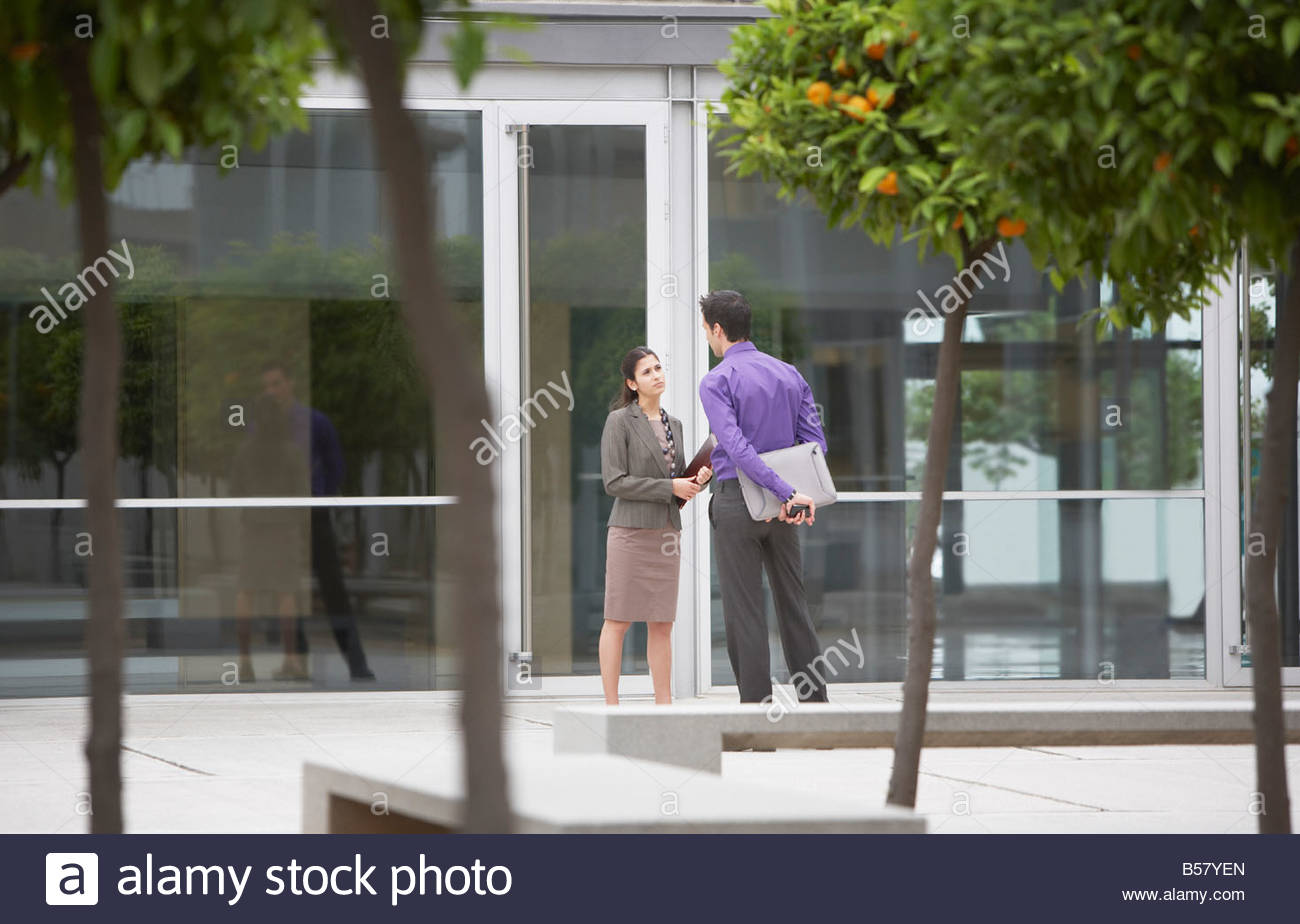 Co-workers talking in office building courtyard - Stock Image