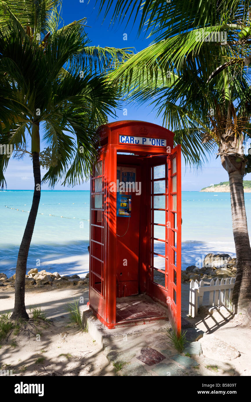 Traditional English red telephone box on the beach at Dickenson Bay, Antigua, Leeward Islands, West Indies, Caribbean - Stock Image