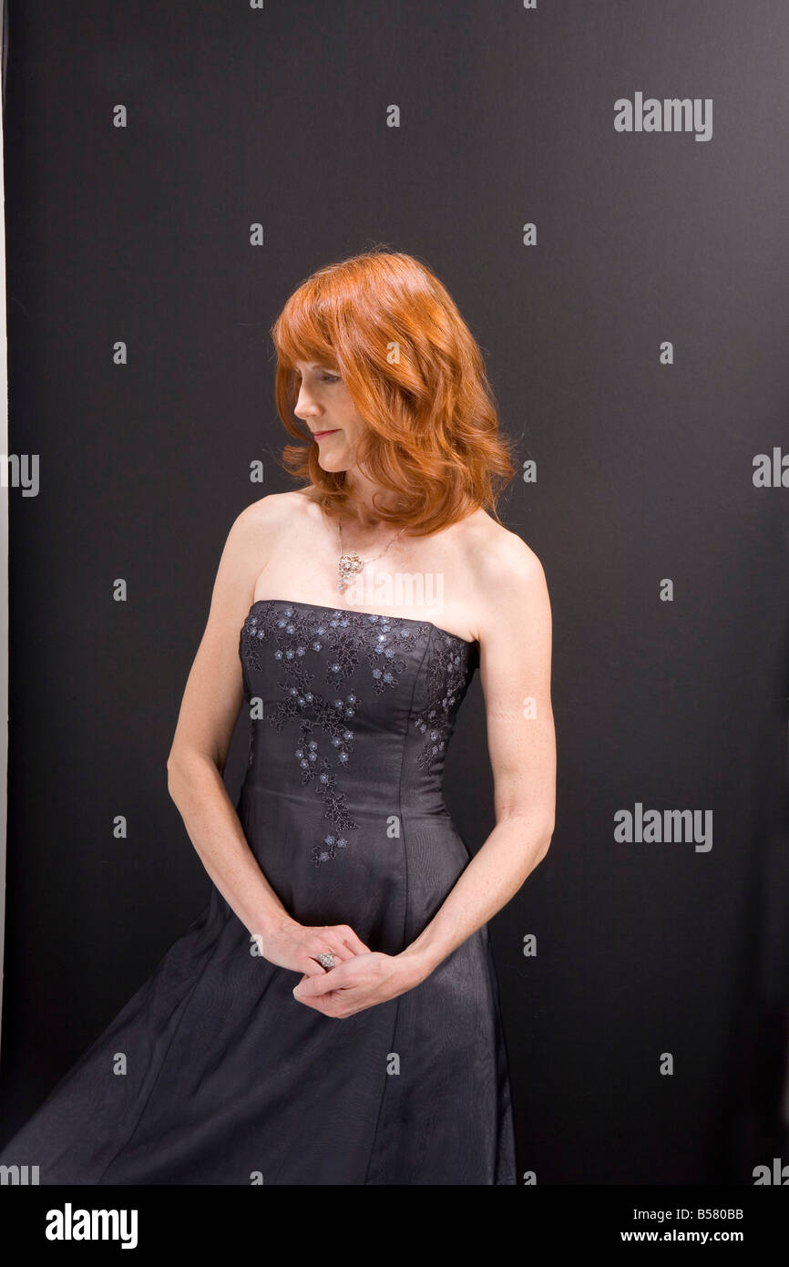 red haired woman poses for portrait in elegant grey strapless dress - Stock Image