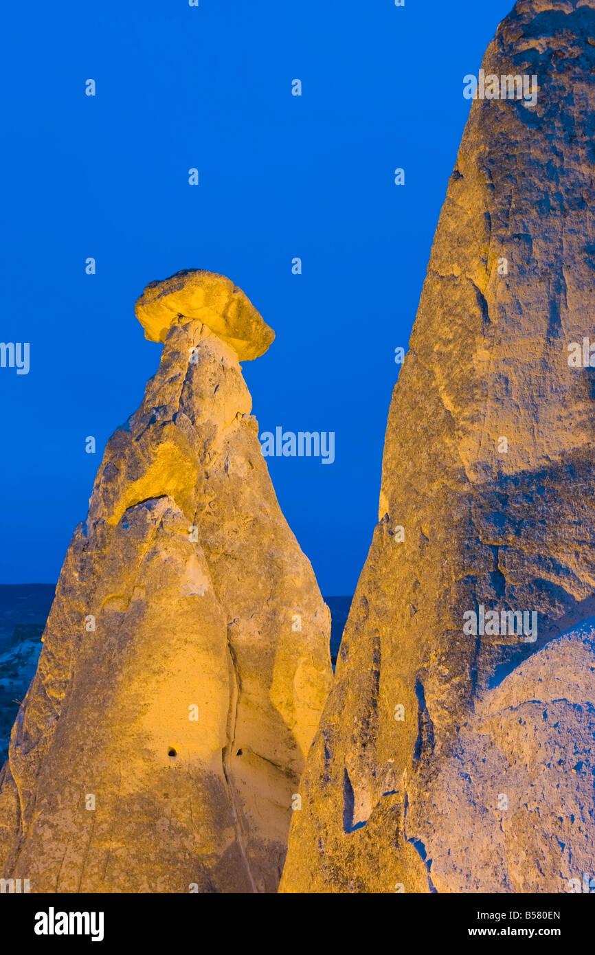 Fairy chimneys known as The Three Beauties illuminated at night near Goreme, Cappadocia, Central Anatolia, Turkey - Stock Image
