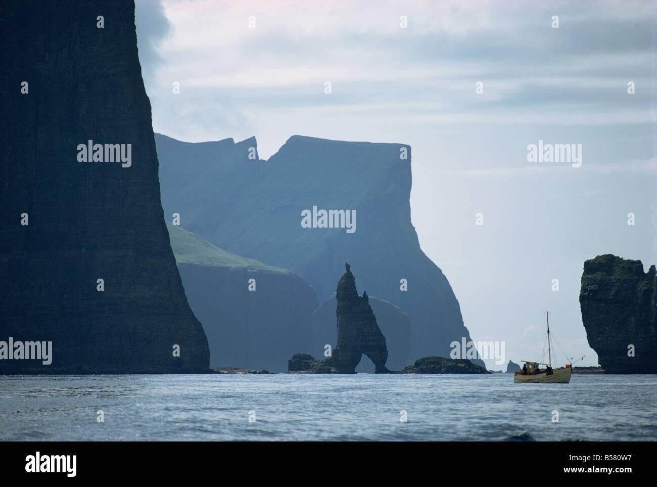 Small fishing boat before a towering cliff coastline, Faroe Islands, Denmark, Atlantic, Europe - Stock Image