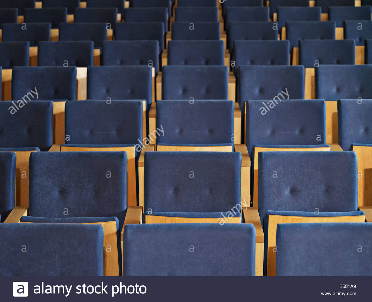 Rows of empty seats in conference room - Stock Image
