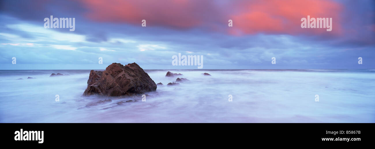 Widemouth Bay at sunrise, with offshore rocks and red storm clouds overhead, near Bude, Cornwall, England, United - Stock Image