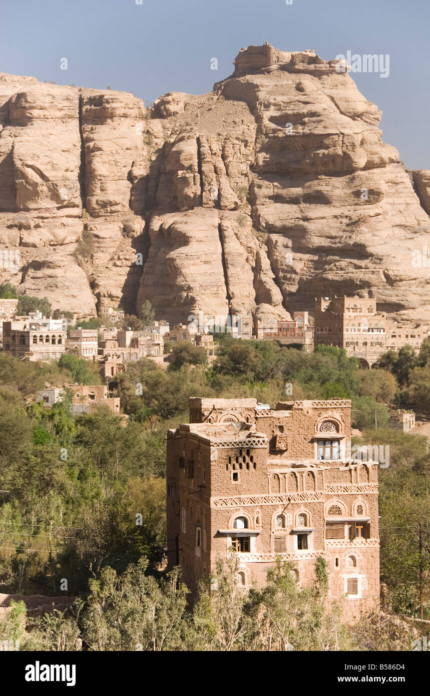 Traditional tall brick-built houses in village beneath sandstone cliff, Wadi Dhahr, near Sana'a, Yemen, Middle - Stock Image