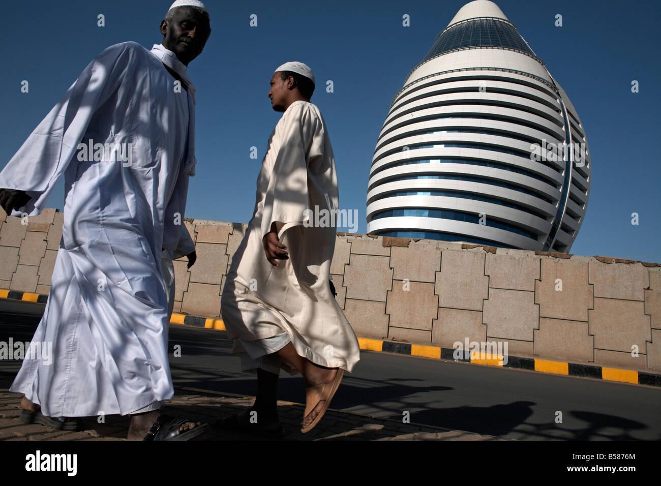 Locals walk past the 5-star Boji Al-Fateh Hotel (Libyan Hotel), designed to represent a sail, Khartoum, Sudan, Africa - Stock Image