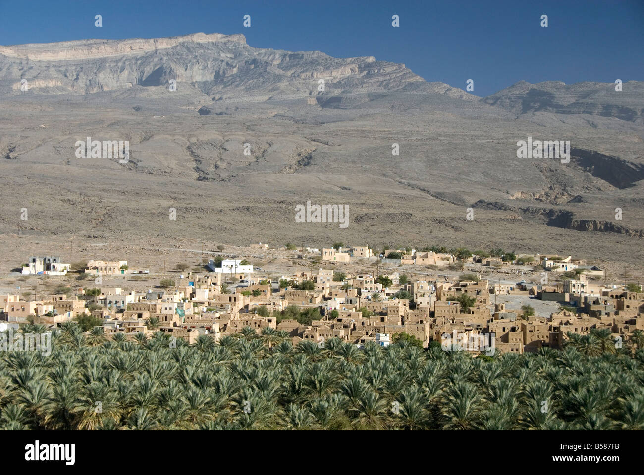 Small town beside its irrigated palmery, Al Hamra, at foot of mountain of Jabal Akhdar, northern Oman, Middle East - Stock Image