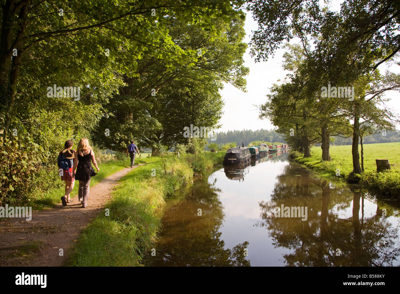 People walking on canal towpath Brecon and Monmouthshire canal Wales UK - Stock Image
