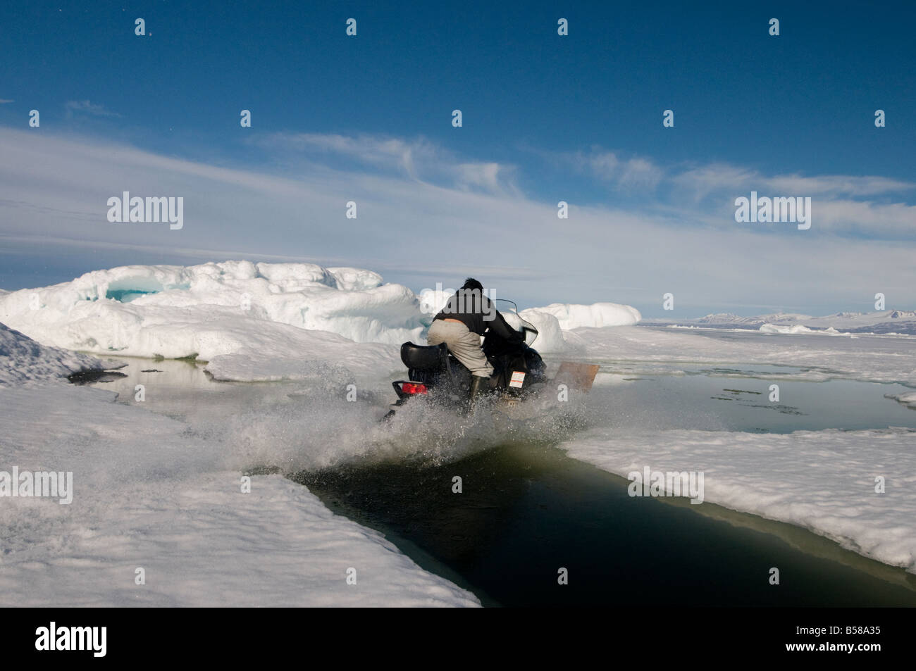 Crossing dangerously wide spring cracks in the ARctic ocean by driving the snowmobile across the surface of the - Stock Image