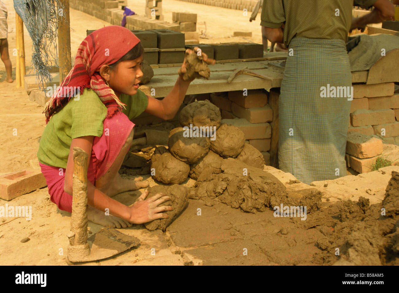 Child labour young girl moulding lumps of clay at brickworks on Mandalay Plains Myanmar Burma Asia - Stock Image
