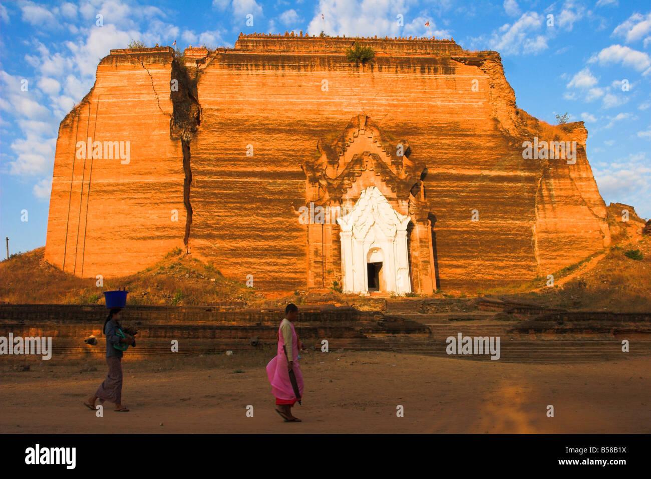 Woman and nun walk past paya damaged by earthquakes Mingun Paya Mingun Mandalay Myanmar Burma Asia - Stock Image