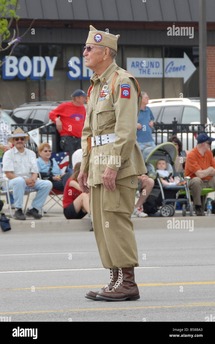 An old war veteran marches in a Memorial Day parade. - Stock Image