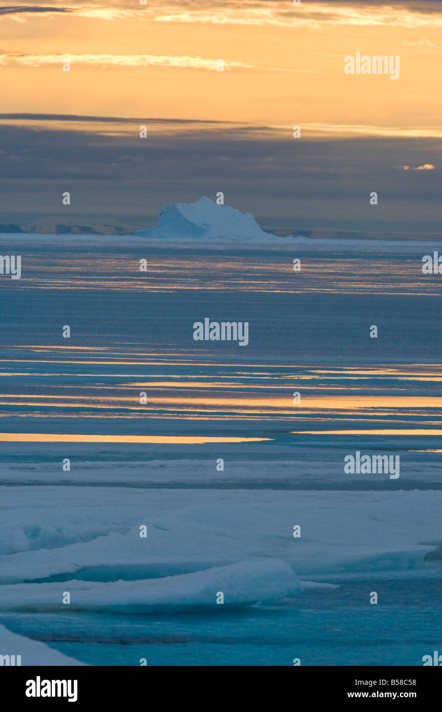 Frozen in iceberg is surrounded by spring melt water at Lancaster Sound Nunavut Canada Arctic. - Stock Image
