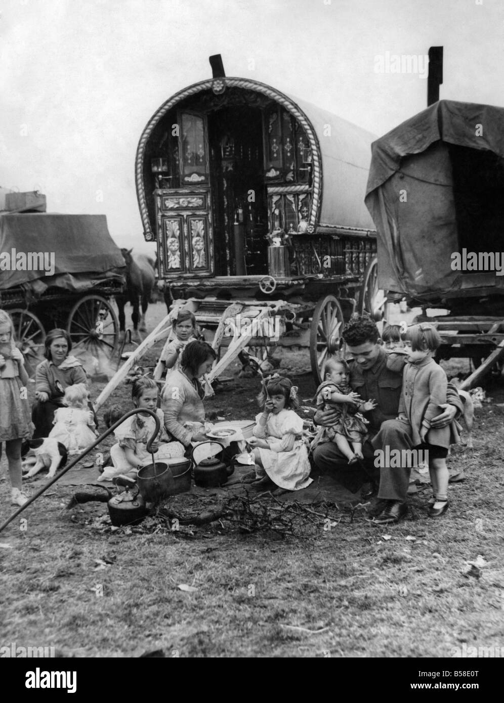 Gipsies Camps. A soldier plays with the children of a Gypsy Campon returning from the Western Front.  January 1945 - Stock Image