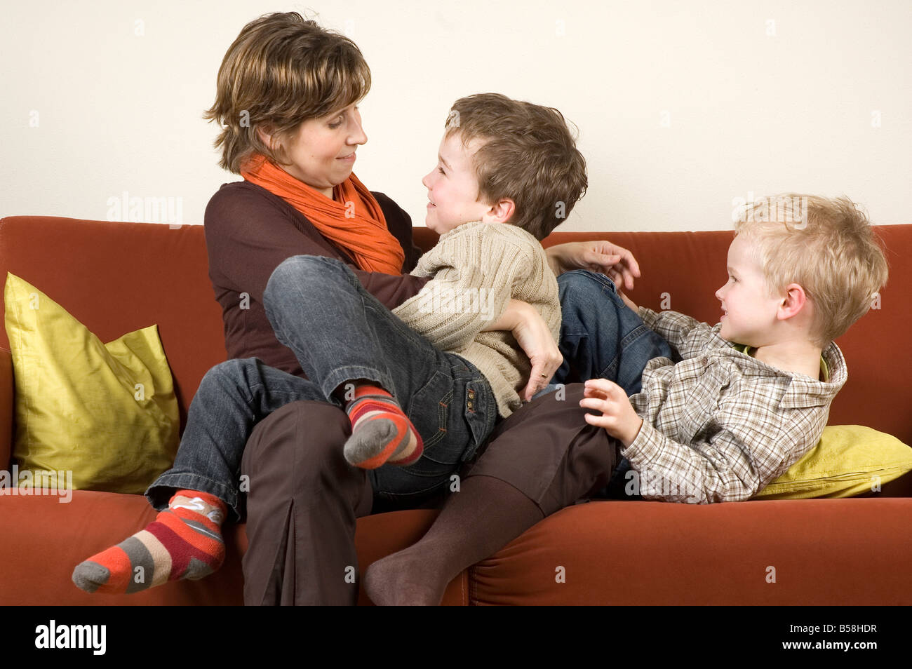 Family playing pranks on a couch - Stock Image