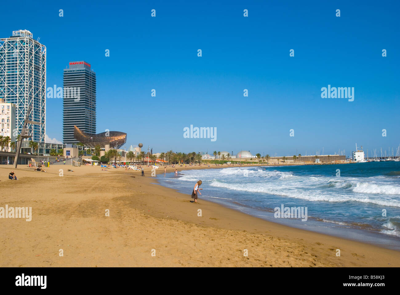 People at Platja de la Barceloneta beach in front of Port Olimpic in Barcelona Spain Europe Stock Photo