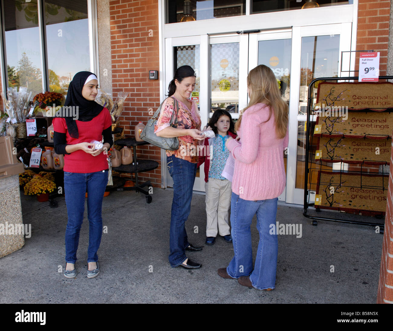 Teenage girls giving away free energy efficient light bulbs to people for an environmental community service project - Stock Image