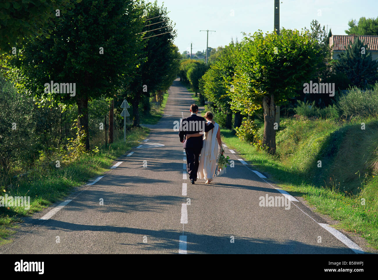 Newly-wed bride and groom walk from village church to reception, Provence, France, Europe - Stock Image