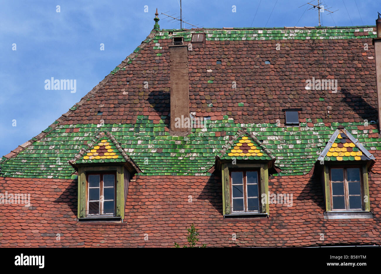 Dormer windows and decorative tiles on a typical roof in the old town of Ribeauville Alsace France G Thouvenin - Stock Image