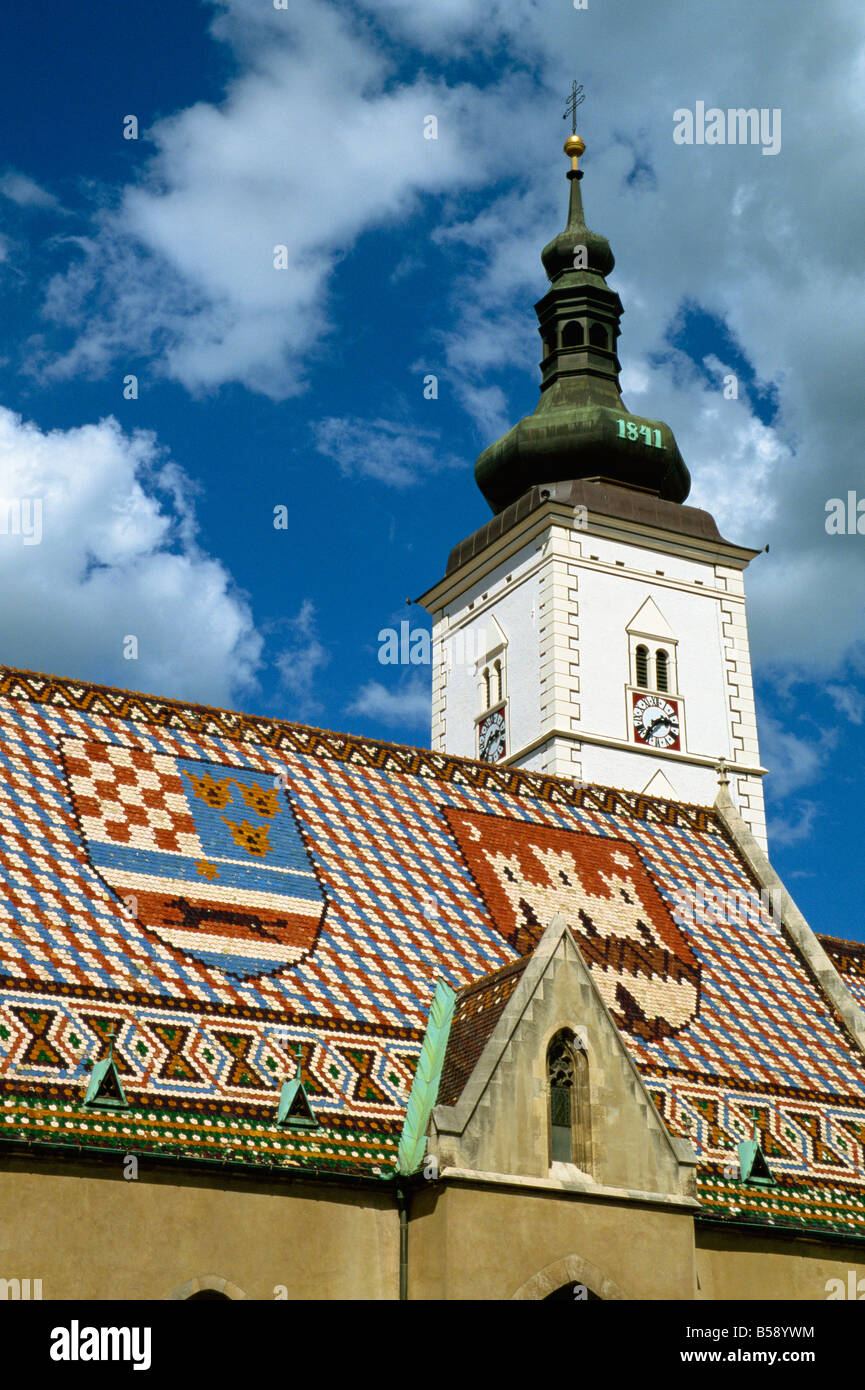 Close up of tile roof with pattern of shields and clock tower of St Marks church Zagreb Croatia Europe - Stock Image