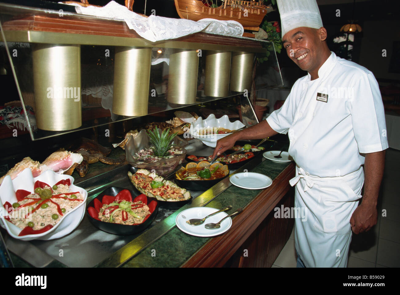 Final touches from chef to seafood buffet, Havana, Cuba, West Indies, Central America - Stock Image