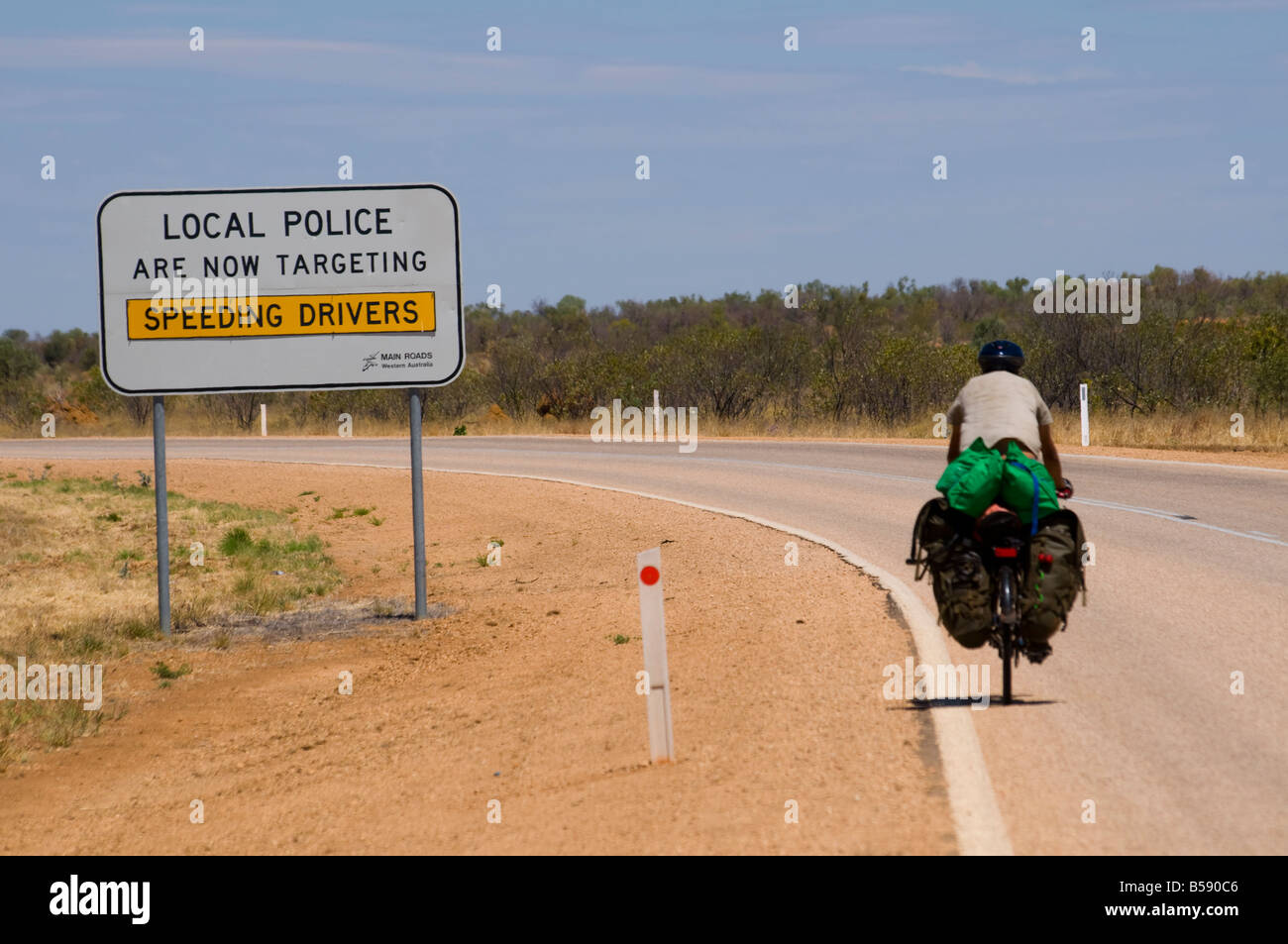 A cyclist riding outback roads in high temperatures near Fitzroy Crossing in the Kimberley region of Western Australia - Stock Image
