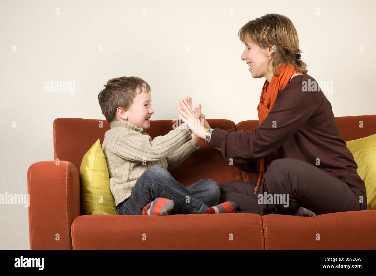 Mother and son are playing a clapping game on the couch - Stock Image