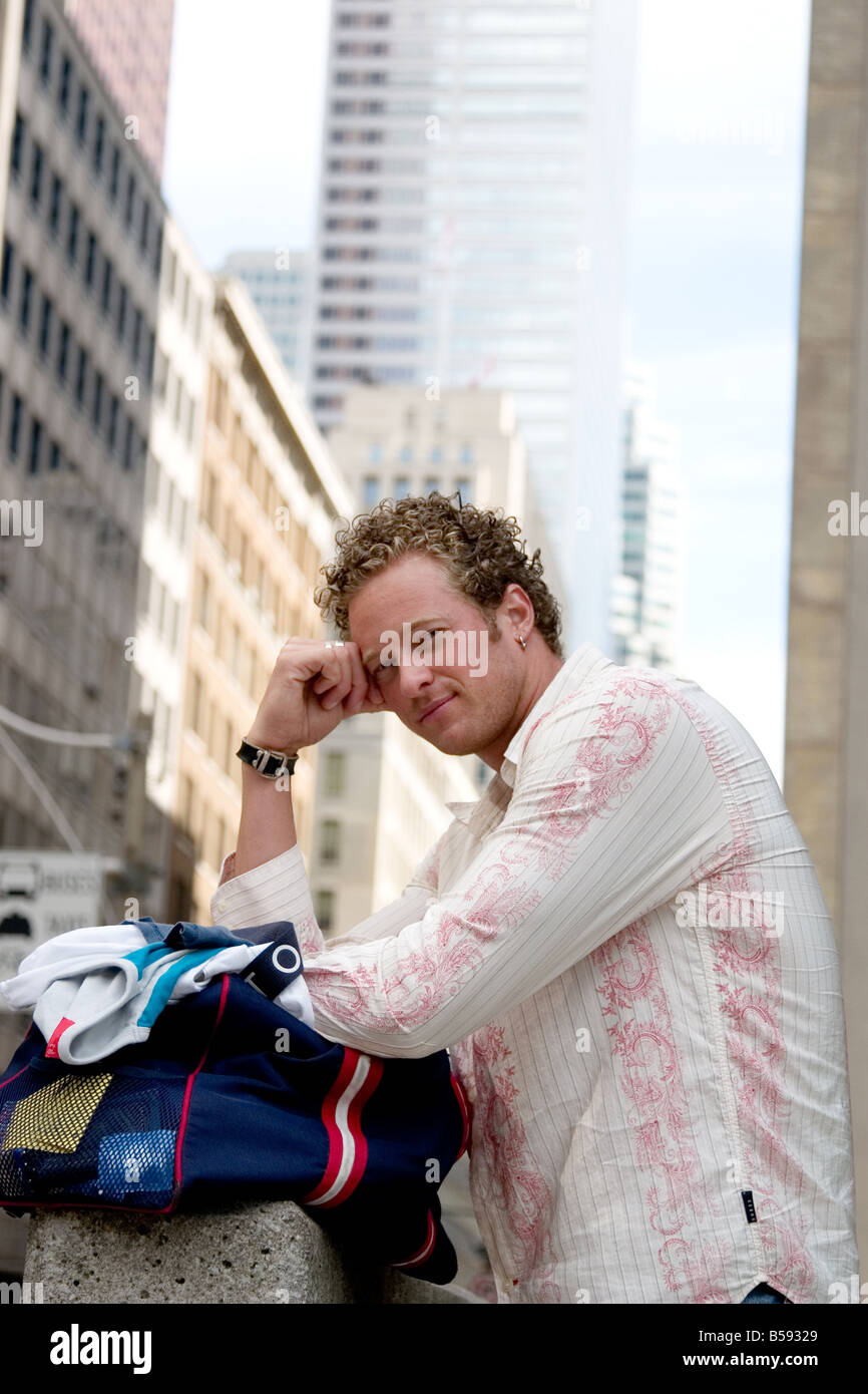 A young man with his clothes bag - Stock Image