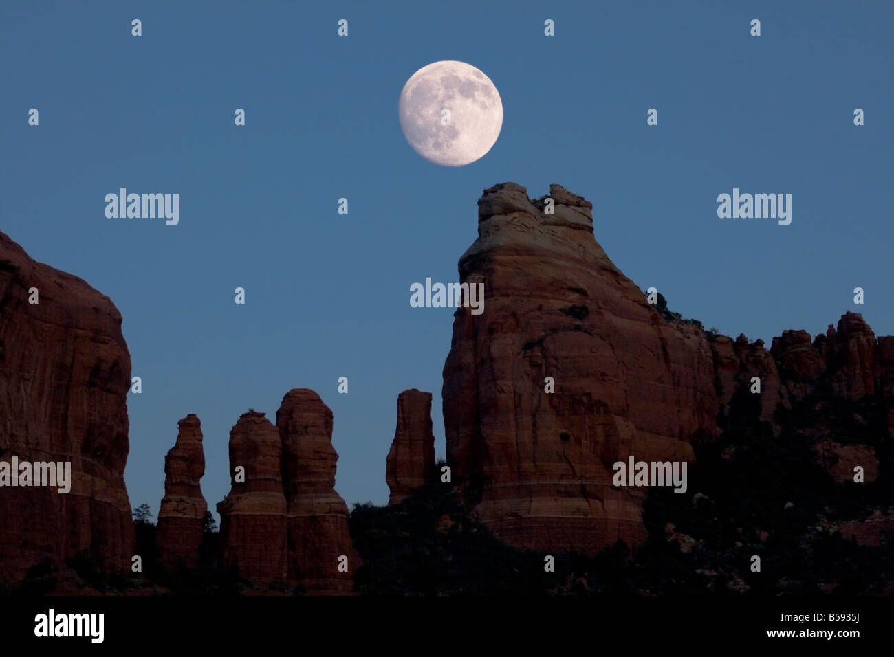 a nearly full moon rises over red rock spires near Sedona Arizona - Stock Image