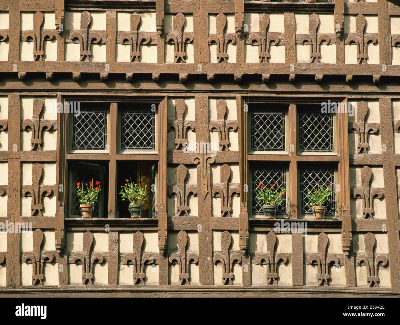 Detail of fleur de lys motif carved in wood on the timber framed Market Hall in the village of Arreau Midi Pyrenees - Stock Image