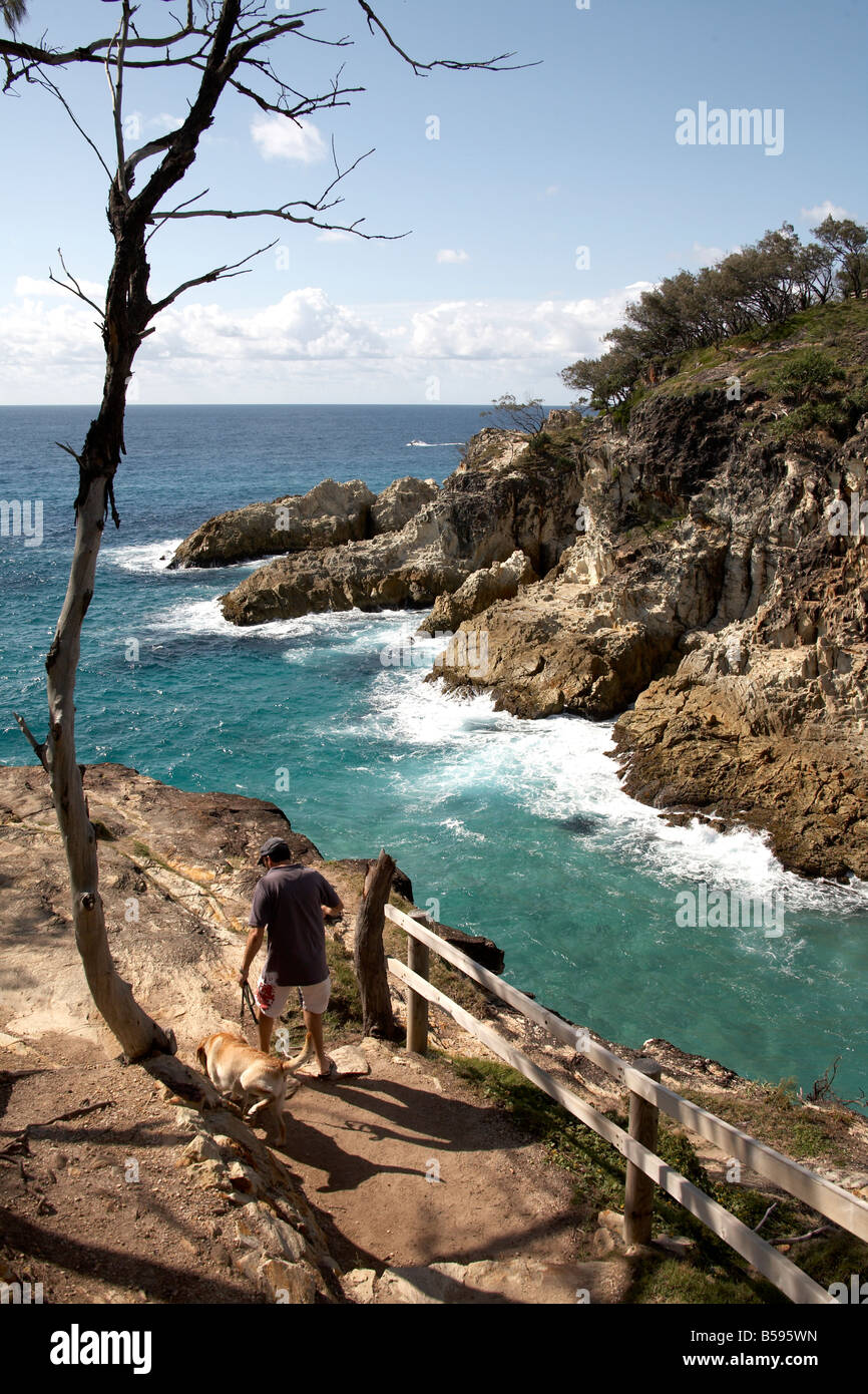 Man with dog by North Gorge sea cliffs on North Stradbroke Island Queensland QLD Australia - Stock Image
