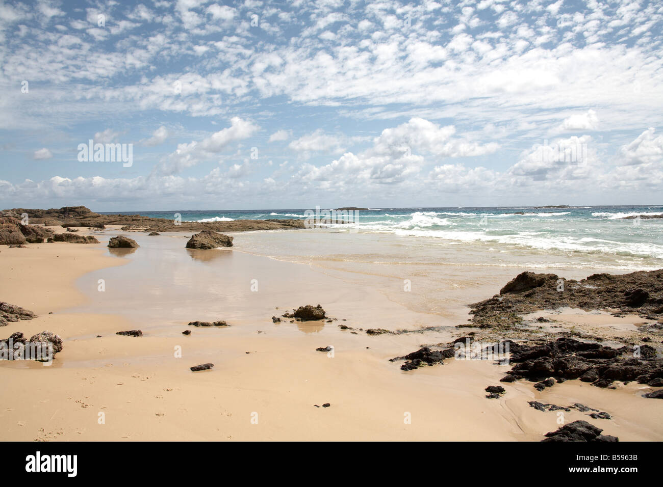 Frenchmans beach with wet sand and rocks on North Stradbroke Island Queensland QLD Australia - Stock Image