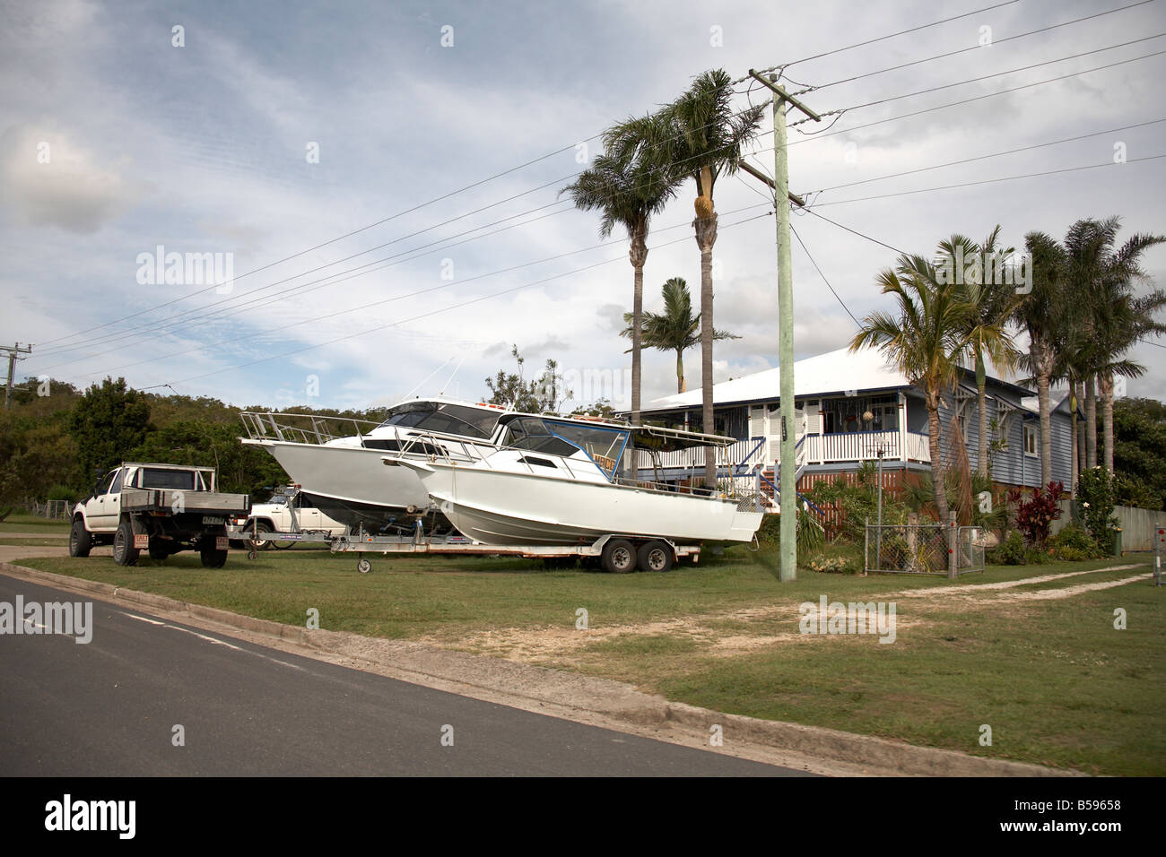 House and boats or with palm trees on Stradbroke Island Queensland QLD Australia - Stock Image