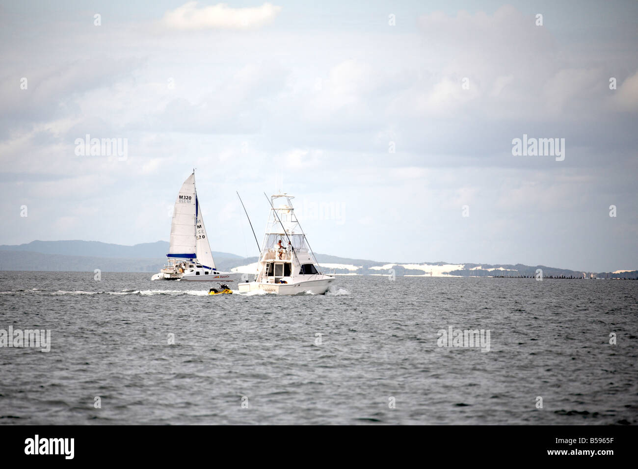 Sailing boat and fishing cruiser on sea with Moreton Island