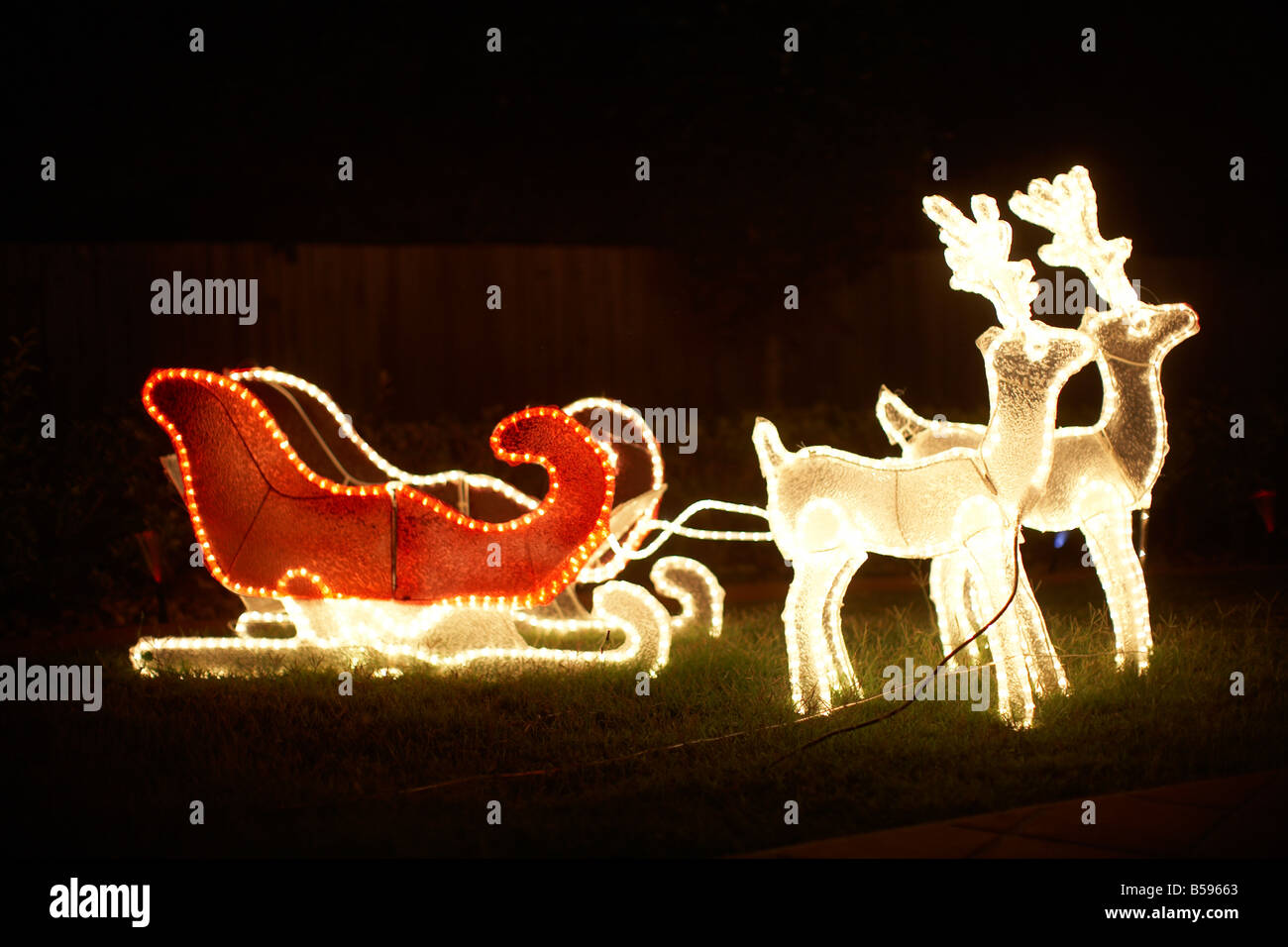 Illuminated christmas light decorations with sleigh and reindeer outside a house in Queensland QLD Australia - Stock Image