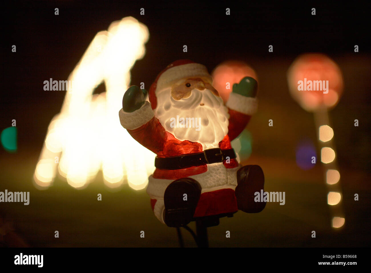 Illuminated christmas light decorations with Father Christmas or Santa Claus outside a house in Queensland QLD Australia - Stock Image
