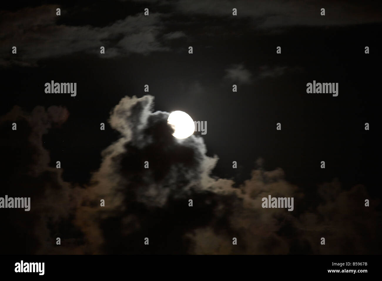 Full moon behind dark scudding clouds at night in Queensland QLD Australia - Stock Image