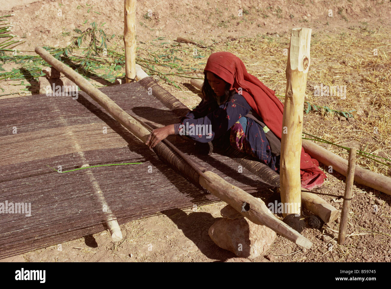 Woman weaving galim, a type of sacking, Afghanistan - Stock Image