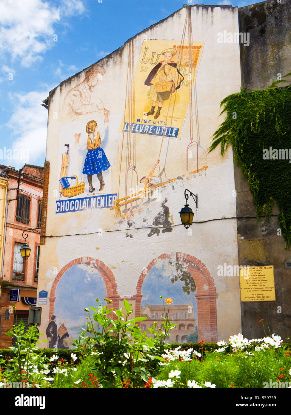 Vintage French advertising posters painted as a street art mural in Moissac, Tarn et Garonne, France, Europe - Stock Image