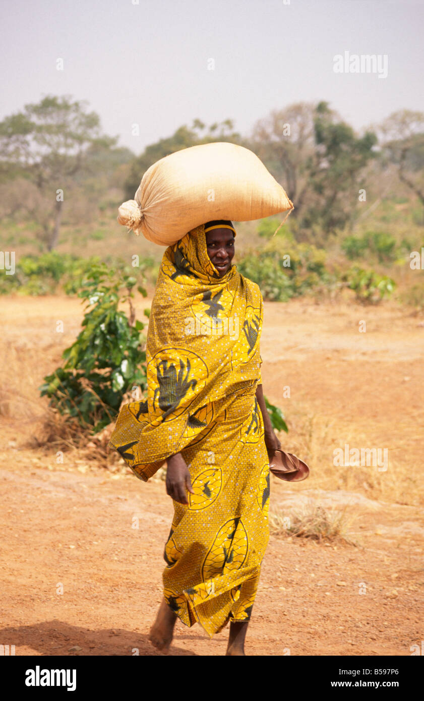 Woman with yellow shawl dress walking carrying a sack on her head Kaduna Nigeria Africa - Stock Image