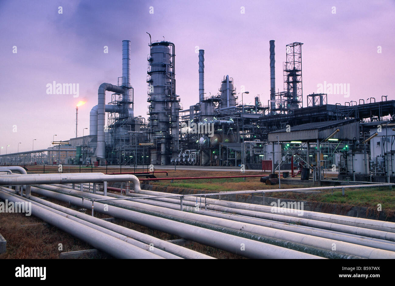 Pipes an installations with purple or mauve sky in NNPC Nigerian National Petroleum Corporation oil refinery in - Stock Image