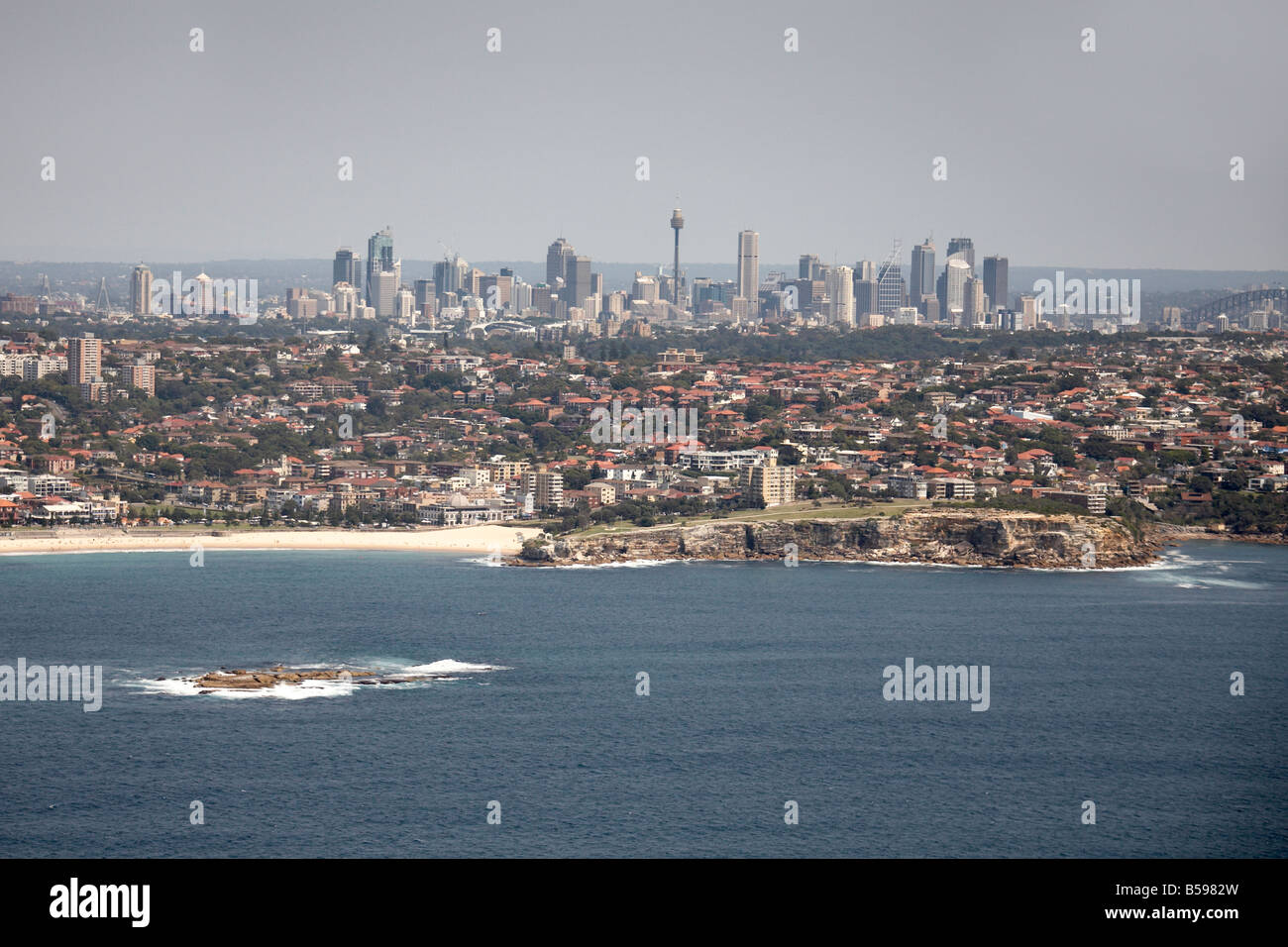 Aerial view north west of Wedding Cake Island Coogee city skyscrapers and Harbour Bridge in distance Sydney NSW - Stock Image