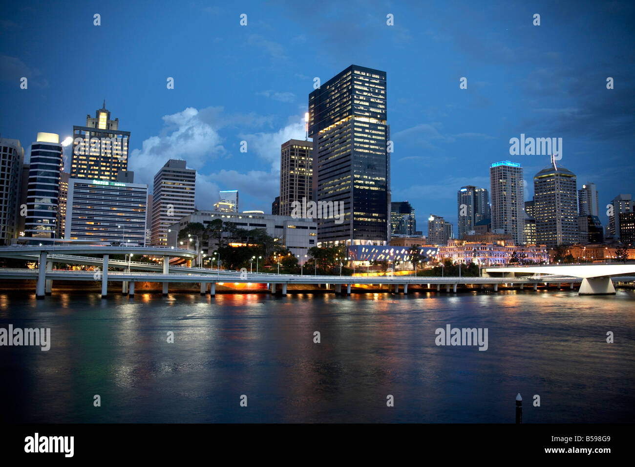 City centre business district waterfront buildings skyline beyond river in evening light in Brisbane Queensland - Stock Image