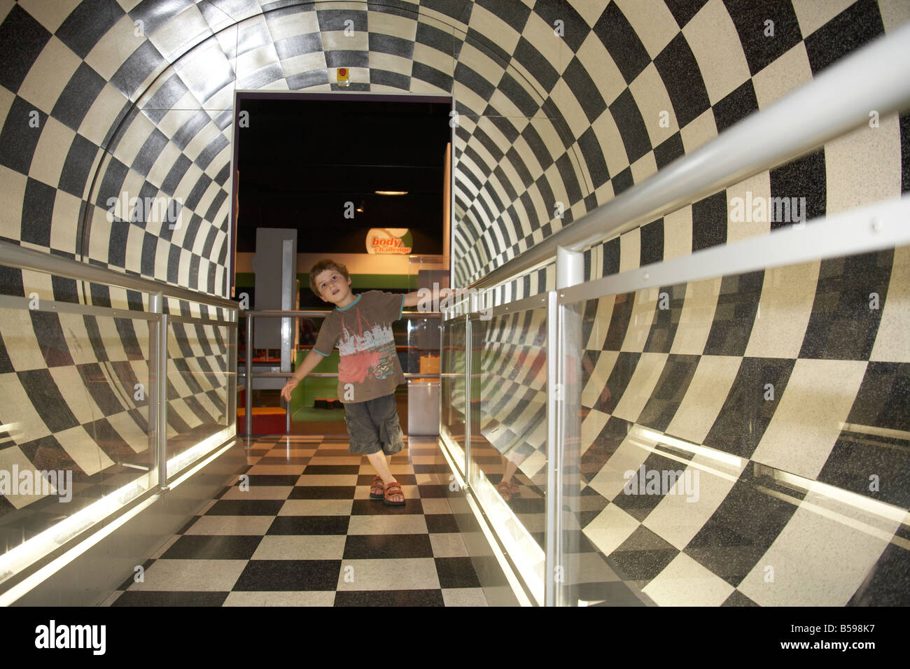 young boy round tube room black white checkerboard in Brisbane Queensland QLD Australia - Stock Image