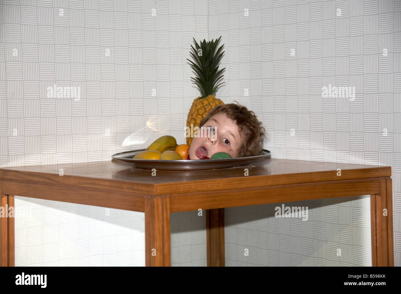 illusion table separate head on plate fruits young boy in Brisbane Queensland QLD Australia - Stock Image